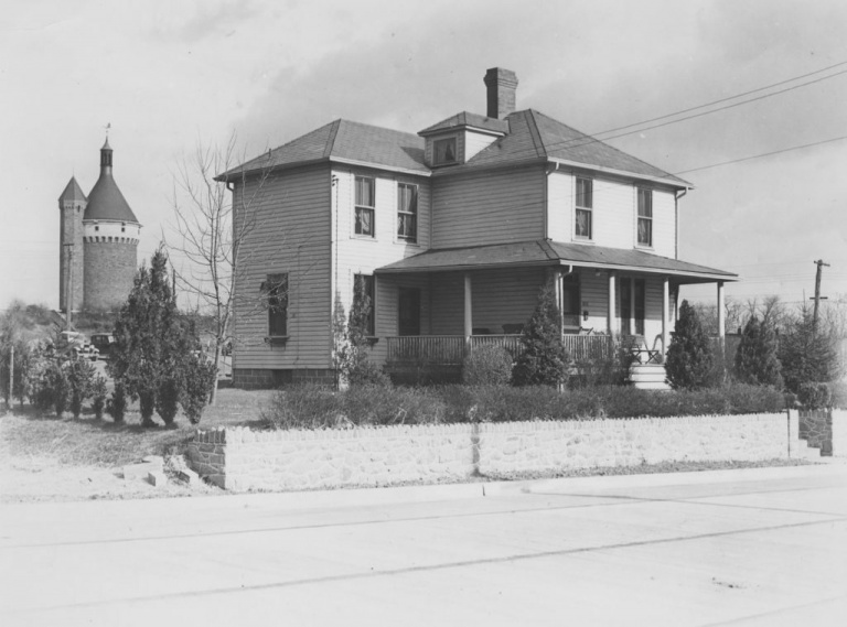 A historical photo from a National Park Service collection shows a Reno City building, with the Fort Reno water tower in the background.